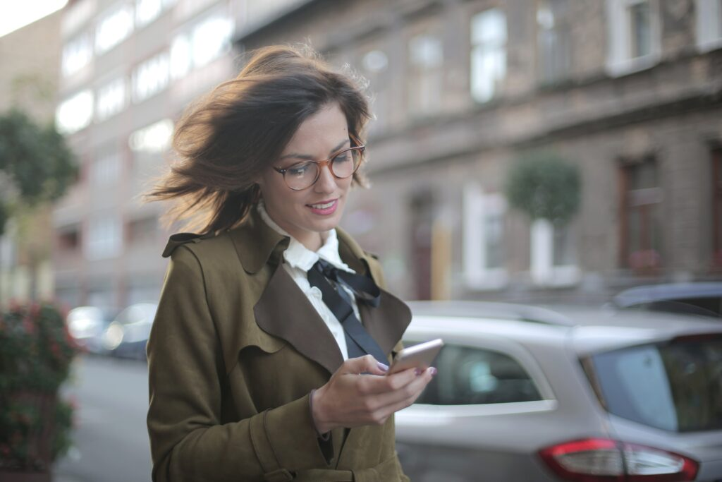 Register an e-commerce business -brunette woman with glassesin a white shirt and tie with a brown trench coat walking along a street using her phone for browsing