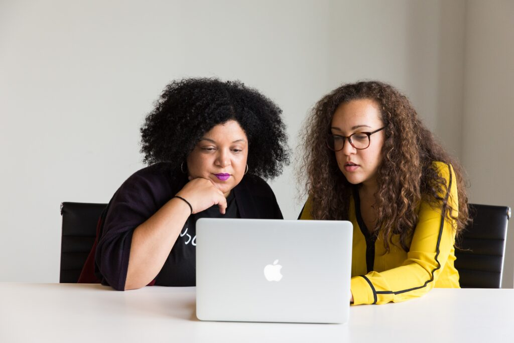 Do you pay VAT on eBay fees - two women, one in black, one in yellow looking at a laptop at a white desk