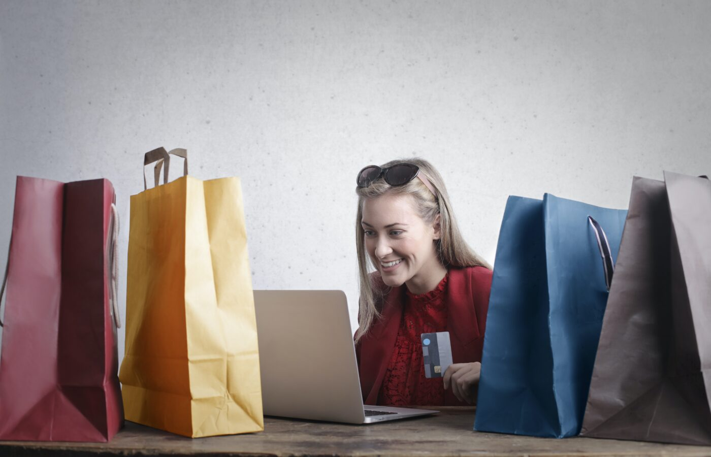 online vs high street shopping - woman sitting at laptop with a credit card surrounded by paper shopping bags