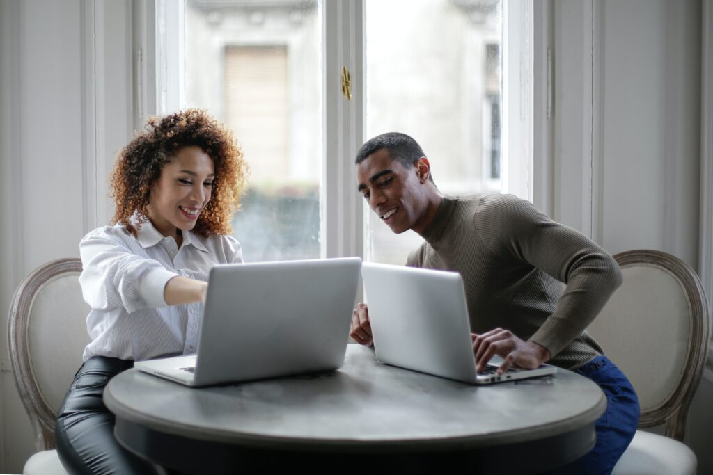 online vs high street shopping - man and woman sitting at a table each with laptop, woman pointing out something on her screen