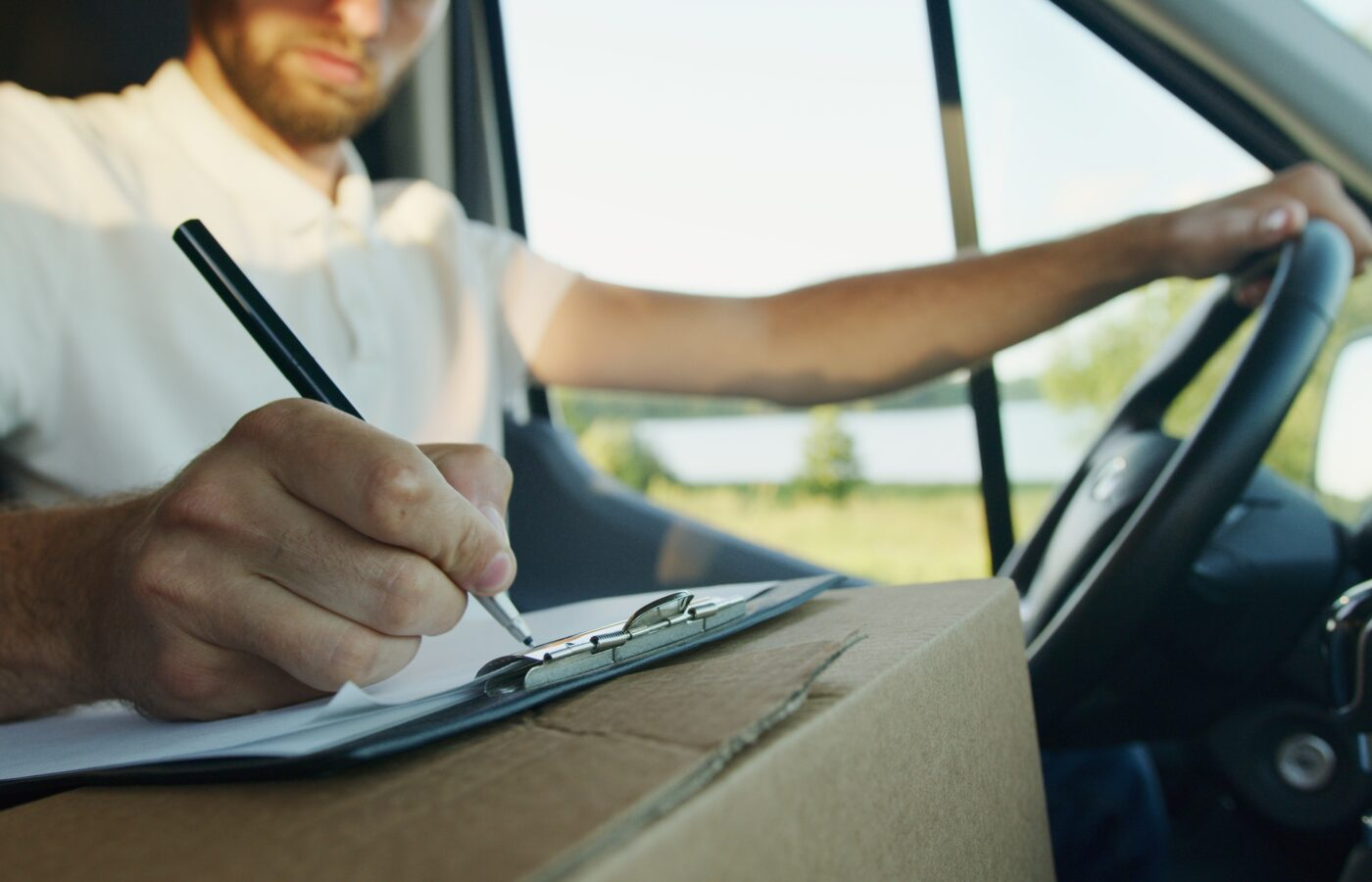 2021 VAT changes - man with arm on the wheel writing on a notepad on a delivery box
