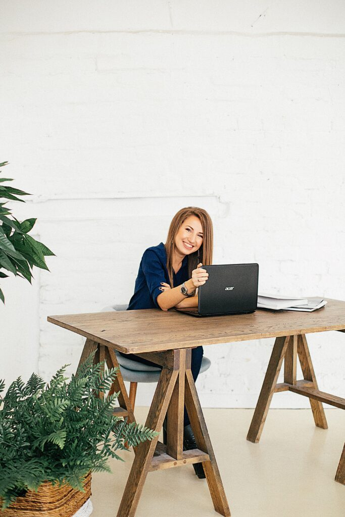 New VAT rules for e-commerce - smiling woman in navy sitting at a wooden desk with laptop in a minimalist office