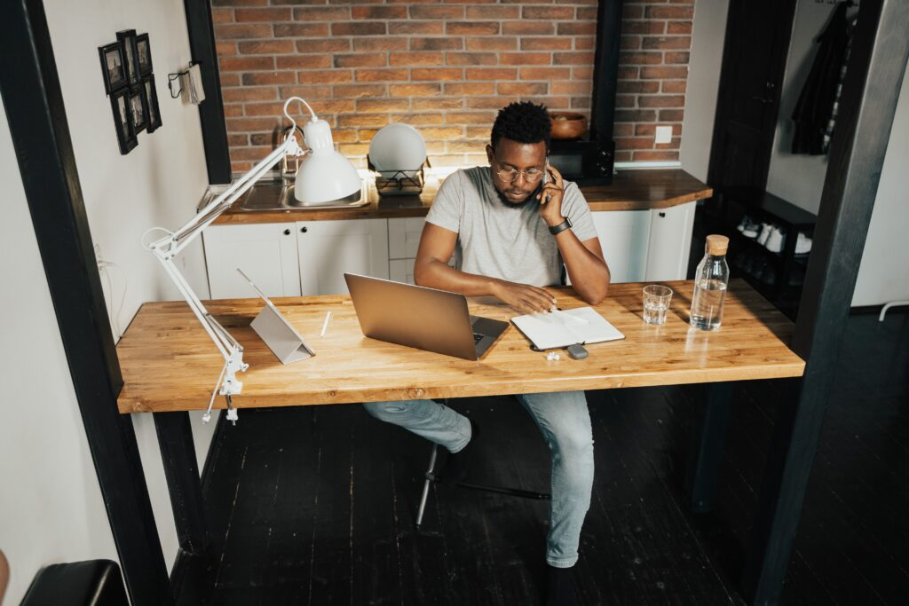 2021 VAT changes - man sitting at a desk at home with a lamp, water bottle, laptop and paperwork