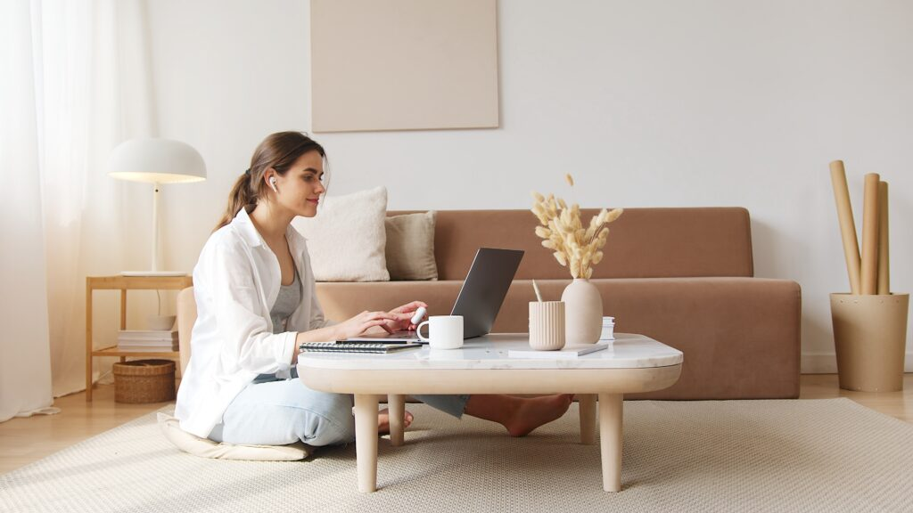 Woman sitting crosslegged on the floor at a Japanese style desk with a laptop in a minimally decorated room