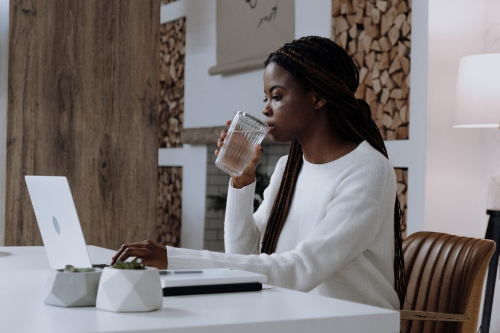 Amazon vs eBay - beautiful woman in a white jumper, drinking a glass of water and working at a minimalist desk