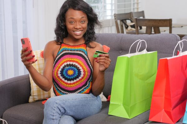 Facebook shops UK - woman in jeans and a hippie top with a phone in one hand and credit card in the other on the sofa with lots of brightly coloured shopping bags