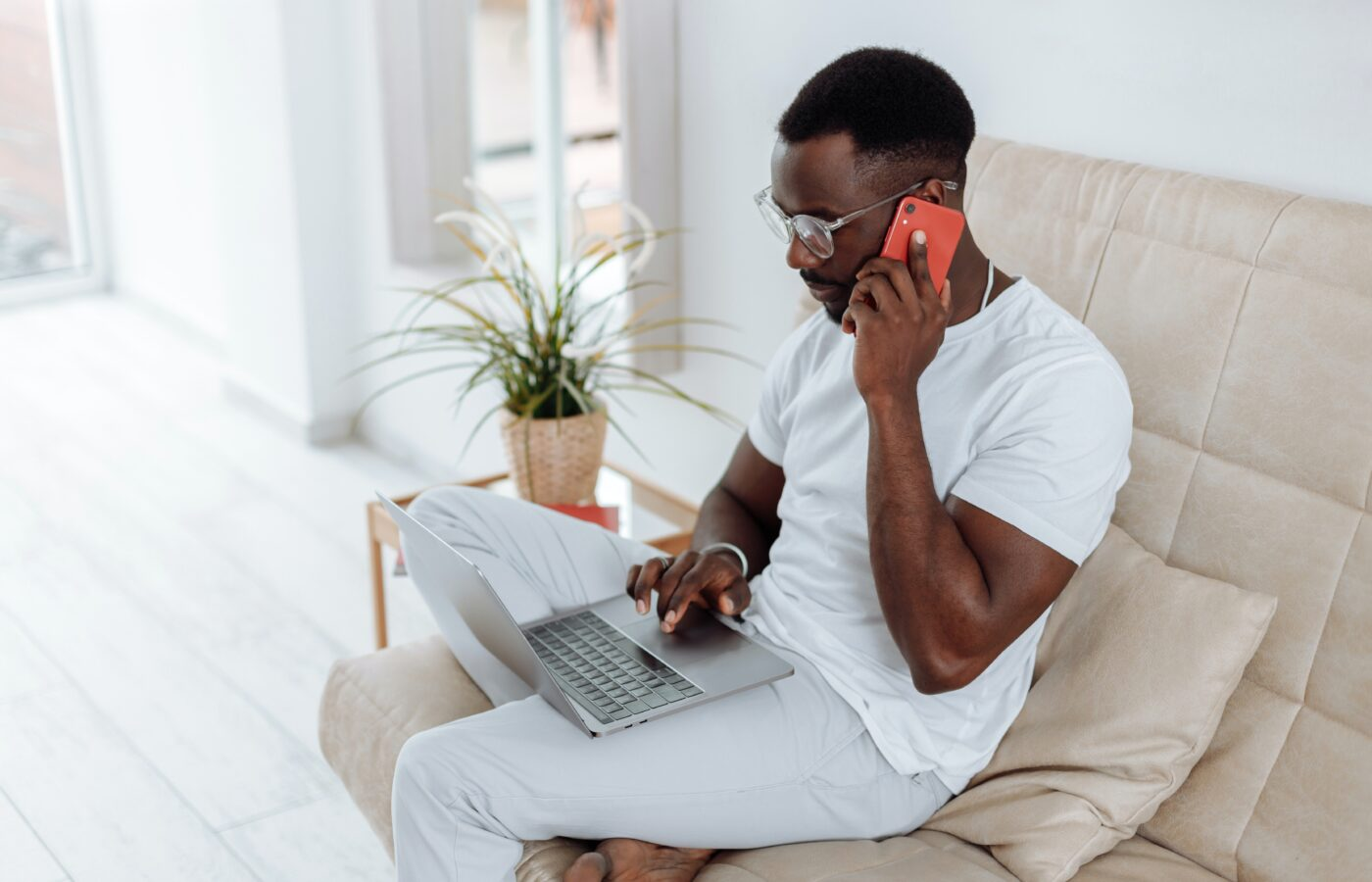 Deferred VAT payment for e-commerce - man dressed in white sitting on a beige armchair in a minimalist room on the phone with a laptop on his lap