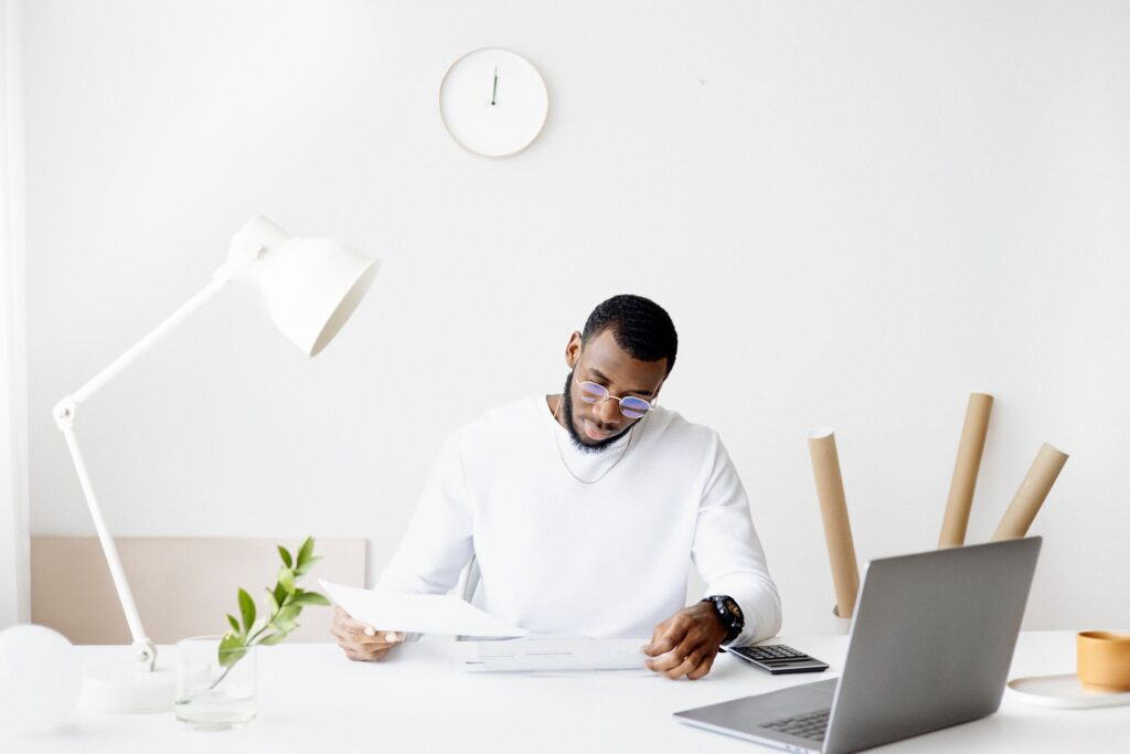 Notify my accountant - man in white in a white minimalist room at a desk looking at paperwork with a laptop in front of him