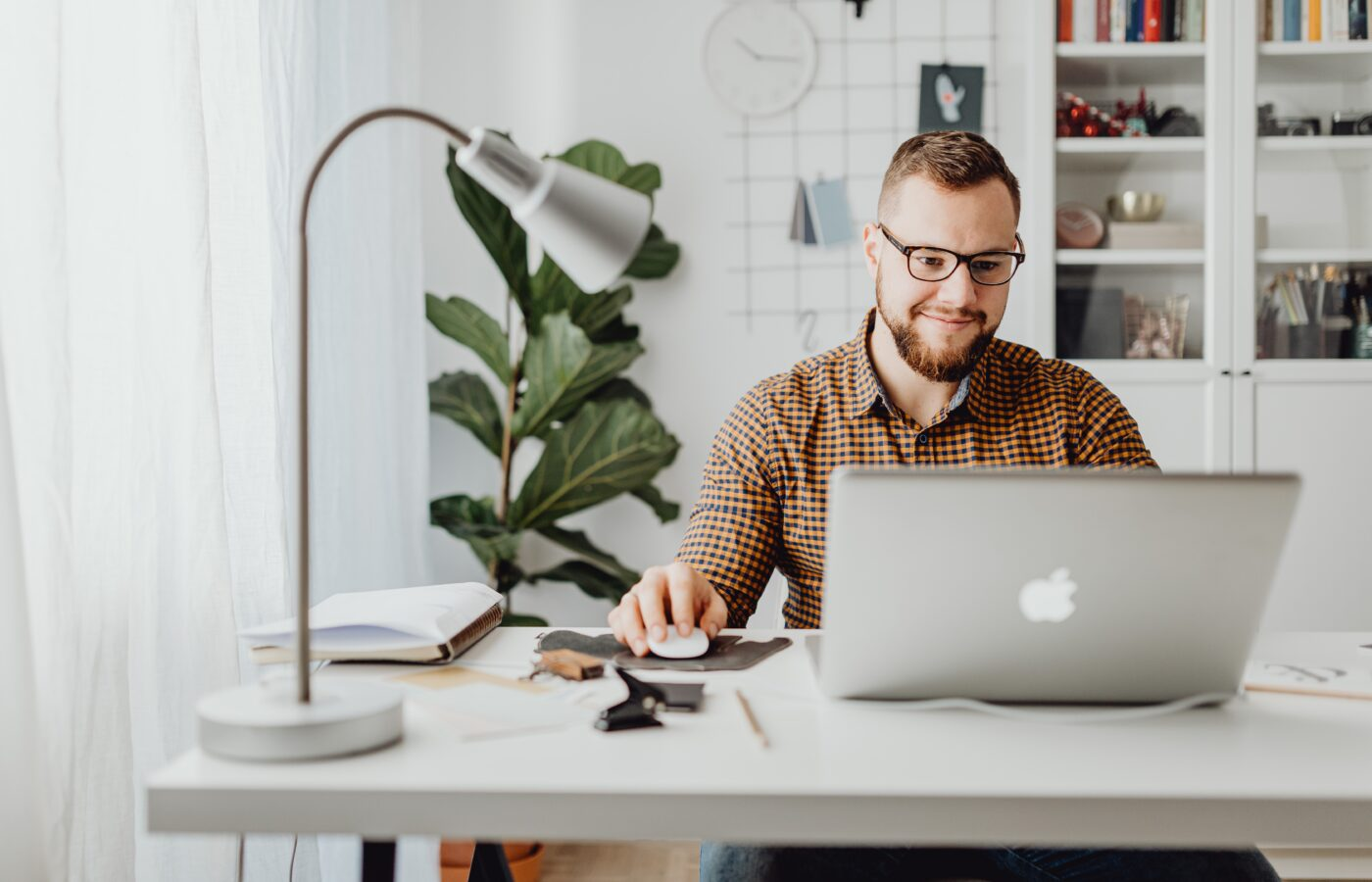 Best accounting software for e-commerce 2021 - man working on a laptop at a minimalist desk with a silver lamp and a green plant and bookcase in the background