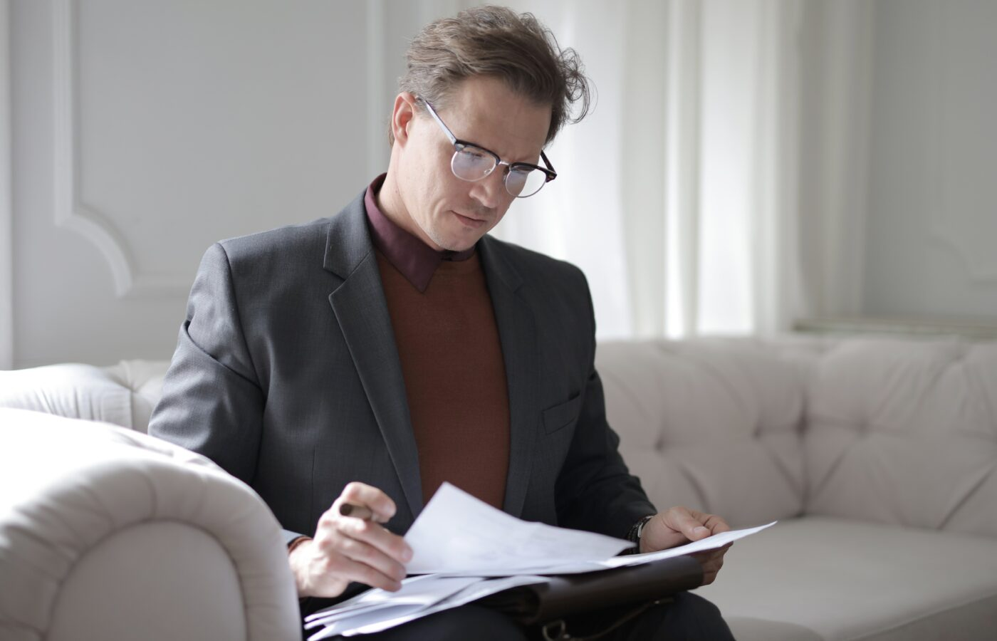 Most efficient way to pay yourself - man in a suit and polo neck with glasses sitting on a beige sofa in a minimalist room reading paperwork