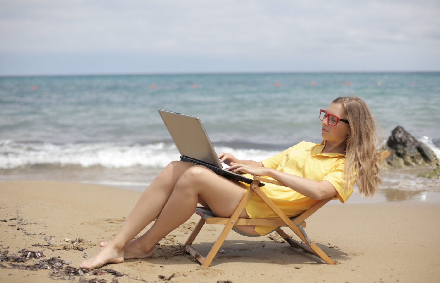 How to automate your e-commerce business - woman working on a laptop in a low deck chair, yellow sun dress, right by the ocean