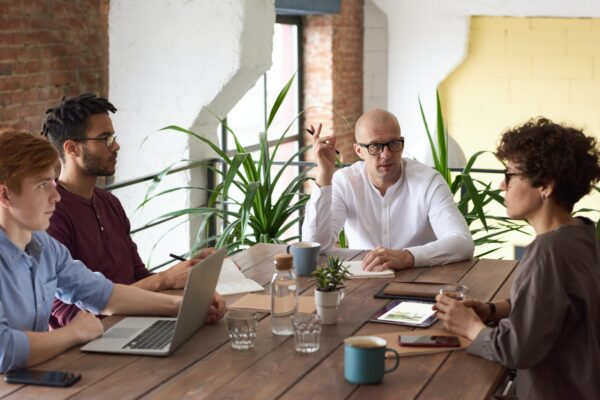 E-commerce due diligence - 4 people sitting at a large wooden table holding a business meeting