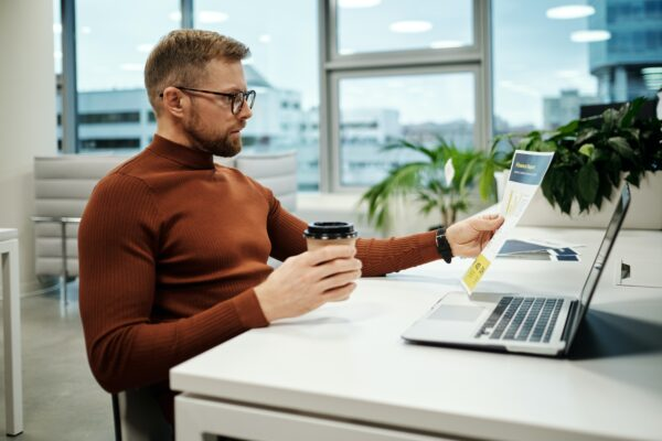 Top Xero integrations for e-commerce - man in a brown tutleneck sitting at a desk with a coffee and a laptop in a spacious office with a huge window
