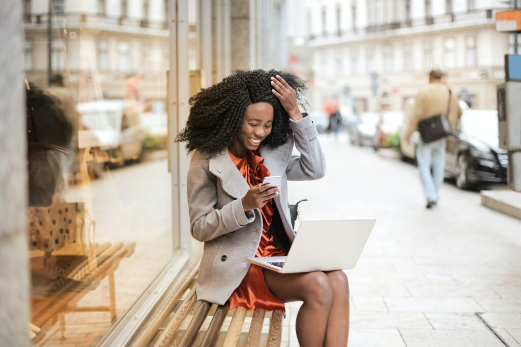 Companies House - woman in an orange mini dress and short grey coat sitting on a bench outside a shop with a laptop on her knee, surprised in a good way by what she sees