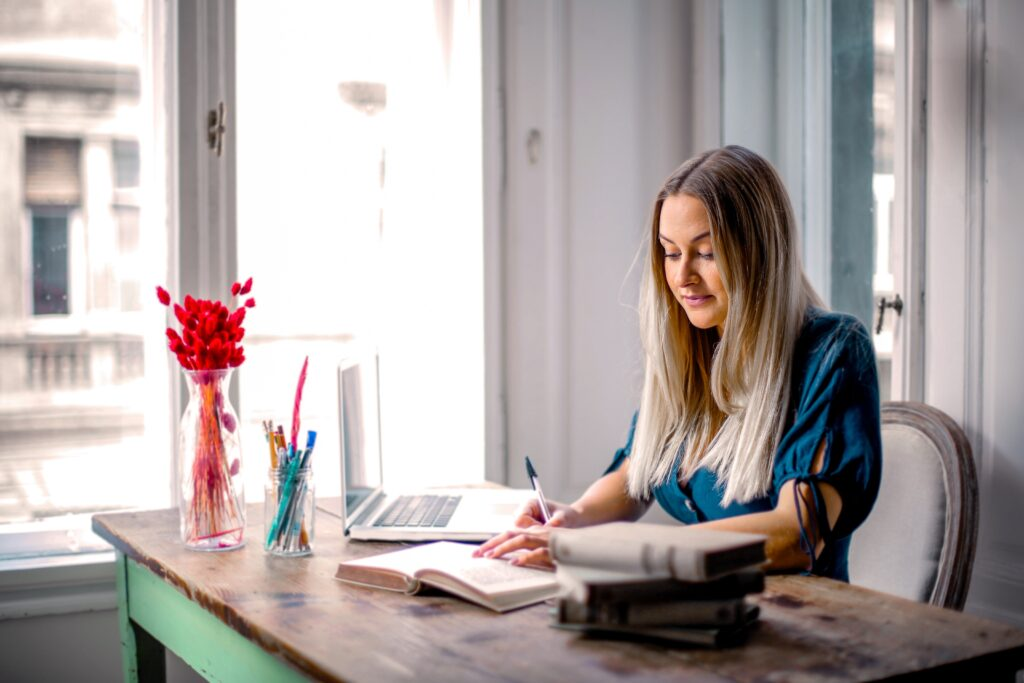 Tax bands and thresholds - blond woman sitting at a desk looking at a notebook with a laptop and other office accessories on her desk