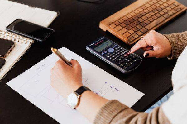 What are e-commerce accountants - woman using a calculator with her right hand and writing with her left on a black desk