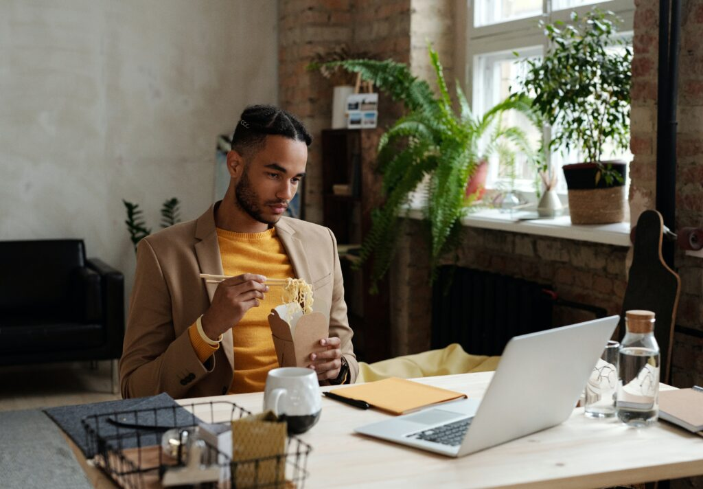 Work from home expenses for e-commerce - man in a suit jacket and tshirt eating noodles out of a wakeaway box and reading something on his laptop at a desk
