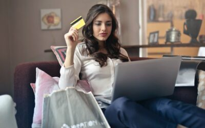 American Sales Tax for e-commerce entrepreneurs - woman with credit card in hand and laptop on her knee surrounded by shopping bags