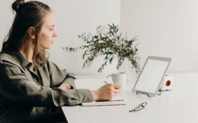 VAT rules for e-commerce - lady sitting at a minimalist desk with a coffee, notebook, tablet propped up to look at the screen and a pot plant in the background