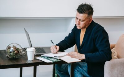 Amazon VAT UK Changes - Man writing in a notebook on a desk with a laptop and coffee