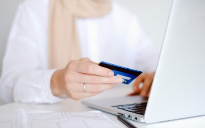GoCardless vs Stripe - woman in white at a white desk with laptop and a credit card in her hand